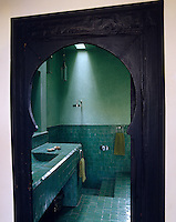 A simple Moroccan bathroom decorated with green ceramic tiles and lit by a skylight over the shower is glimpsed through an arched doorway