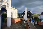 "Portmeirion, in North Wales, is a resort, where no one has ever lived. A self-taught Welsh architect named Sir Clough Williams-Ellis built it out of architectural salvage between the 1920s and 1970s, loosely based on his memories of trips to Portofino. Including a pagoda-shaped Chinoiserie gazebo, some Gothic obelisks, eucalyptus groves, a crenellated castle, a Mediterranean bell tower, a Jacobean town hall, and an Art Deco cylindrical watchtower. He kept improving Portmeirion until his death in 1978, age 94. It faces an estuary where at low tide one can walk across the sands and look out to sea. At high tide, the sea is lapping onto the shores. Every building in the village is either a shop, restaurant, hotel or self-catering accomodation. The village is booked out at high season, with numerous wedding receptions at the weekends. Very popular amongst the English and Welsh holidaymakers. Many who return to the same abode season after season. Hundreds of tourists visit every day, walking around the ornamental gardens, cobblestone paths, and shopping, eating ice-creams, or walking along the woodland and coastal paths, amongst a colourful assortment of hydrangea, rhododendrons, tree ferns and redwoods. The resort boasts two high class hotels, a la carte menus, a swimming pool, a lifesize concrete boat, topiary, pools and wishing wells. The creator describes the resort as ""a home for fallen buildings,"" and its ragged skyline and playful narrow passageways which were meant to provide ""more fun for more people."" It does just that.///View from the Dome Gallery across the village with the estuary behind, at sunset"