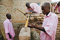 Rwanda. Southern province. District of Muhanga. Central jail of Gitarama. A group of black teenager boys, wearing the pink prisoner's clothes, build a bricks walll during their weekly class in masonry. Air level and plumb level. Minors block. Minors in detention. Detention pending trial and after trial, sentenced to prison. The non-governmental organization (NGO) Fondation DiDé - Dignité en détention runs the Encademi (Encadrement des mineurs) program. Prison centrale de Gitarama. Quartier des mineurs.  © 2007 Didier Ruef