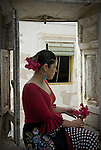 A young Spanish woman sits in a window, holding flowers