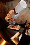 Yudai Hanno, head chef at Ukai-tei teppanyaki restaurant, prepares steak on a griddle at the restaurant in Omotesando district of Tokyo.