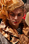 A girl wears a costume of gold and brown with a beaded hat in the New York City Easter Parade