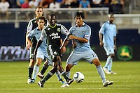 Diego Chara (21) midfielder Portland Timbers passes the ball away from Roger Espinoza Sporting KC... Sporting Kansas City defeated Portland Timbers 3-1 at LIVESTRONG Sporting Park, Kansas City, Kansas.