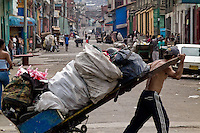 A Colombian garbage recollector pulls his fully loaded cart on the street in the slum of Calvario, Cali, Colombia, 5 April 2004. Calvario, a slum right in the centre of the city, is considered the social bottom of Cali society. Poor dwellers recollect the garbage in the near city centre to sell it for recycling, while their children get high by sniffing the shoe glue on the dirty streets of ghetto. The order in Calvario is maintained by the illegal authorities, usually former policemen or army members, who set their own rules. Criminality, drug abuse, unemployment never allow the slum people jump off the misery and stop being the second category citizen within the rigid society of Colombia. Although Christian missionary organizations attempt to provide help, the overall situation does not improve.