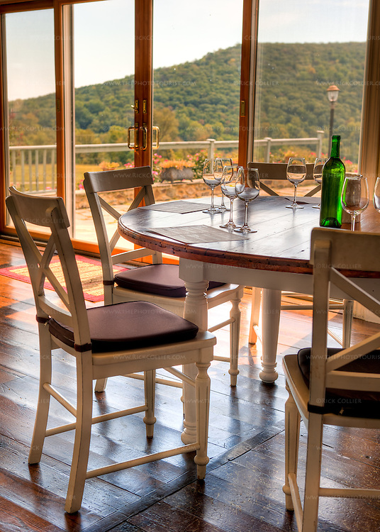 A set table in the dining room at Hillsborough Vineyards offers scenic views of the patio and the valley beyond.