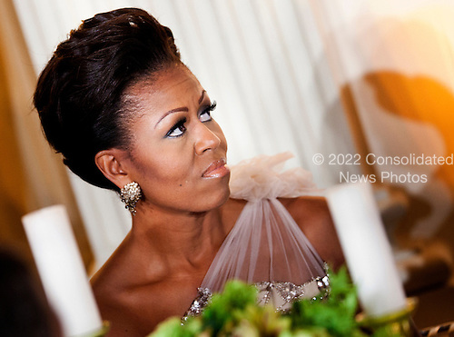 First lady Michelle Obama listens to President Barack Obama speak in the State Dining Room of the White House February 26, 2012 in Washington, DC.  President Obama and first lady Michelle Obama hosted 2012 Governors Dinner which coincides with the yearly meeting of the National Governors Association meeting in DC. .Credit: Brendan Smialowski / Pool via CNP