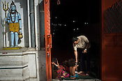 A devotee gives alms to poor at the Hanuman Temple in Govind Puri, New Delhi, India. Photo: Sanjit Das/Panos