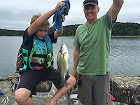 NWA Democrat-Gazette/FLIP PUTTHOFF <br /> Parker Moore, 10, and his dad, Monte Moore of Bentonville, show a white bass Parker caught on a jigging spoon Aug. 15 2016 at Beaver Lake. Jigging spoons may produce a mixed catch of white bass, walleye, catfish and other species during summer and early autumn.