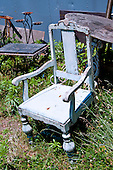 Long Island, New York. West Hampton - blue chair lying in a junkyard.