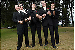 A groom is happily supported by his groomsmen during a fun group shot.