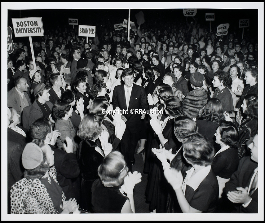 BNPS.co.uk (01202 558833)<br /> Pic: RRAuction/BNPS<br /> <br /> Kennedy in the center of a crowd at a 'Youth for Kennedy' rally during his 1952 senatorial campaign.<br /> <br /> Incredibly-rare photos highlighting the first foray into politics for John F. Kennedy that would eventually cost him his life have come to light.<br /> <br /> The 100 black and white snaps show a youthful-looking JFK from 1946, when he was campaigning to become a US congressman for the first time.<br /> <br /> The tragic future president is seen during an oration lesson where he was given help by an expert with public speaking and posture.<br /> <br /> The 29-year-old is also depicted mingling with the public at an annual parade and as well as celebrating his first political victory - a congressional primary vote - in June 1946.<br /> <br /> The images are being sold by US-based RR Auction.