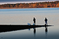 Fishermen a stand on a narrow slit of land where they fish a as the sun sets in the fall.