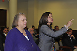 Nassau County Legislature, controlled by Republicans, votes along party lines to consolidate 8 police precincts into 4, on Monday, March 5, 2012, at Mineola, New York, USA. Milagros Vicente (right, pointing finger), a North Valley Stream resident, was one of those shouting out in audience after a Yes vote by one of the legislators.