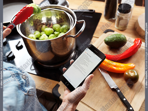 Woman cooking in the kitchen reading a recipe from iPhone 7 in her hand