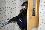 A woman police officer in training holding a paint ball simulated gun clearing a classroom in a school shooting scenario