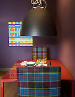 "The table in the dining room is made from lacquered steel and glass and the Louis XIII chairs have been covered in the Anderson tartan, the only tartan with seven colours; the painting on the wall is entitled ""Munchkindland"" by Aurelio Sartorio"