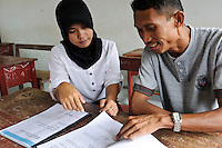 Bapak Juanda Datundugon discussing the environmental education curriculum with a teacher, Dudepo, Bolmong Selatan, Sulawesi, Indonesia.
