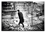 Wushan resident climbs up through the debris of the old town.  Meanwhile the demoition proceeds below.  Three Gorges of the Yangtze River, China.