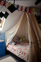 A child's bedroom in the attic is decorated with colourful paperchains