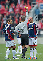 14 April 2012: Chivas USA midfielder Ryan Smith #22 is shown a yellow card by  referee Mark Geiger during a game between Chivas USA and Toronto FC at BMO Field in Toronto..Chivas USA won 1-0.