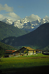 Horses in paddock with farm buildings, forests and mountains in the background. Imst district, Tyrol, Tirol, Austria.