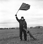 Hare Coursing...On a bitterly cold February day members of the Swaffham Coursing Club meet near Narborough, Norfolk. The judge on horseback monitors each course. He carries with him a small red and white flag, which he waves to indicate to the flagman which greyhound has won. The flagman then flies the appropriate coloured flag...Hunting with Hounds / Mansion Editions (isbn 0-9542233-1-4) copyright Homer Sykes. +44 (0) 20-8542-7083. < www.mansioneditions.com >.
