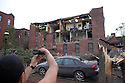 Onlookers snap pictures of storm damage on Hubbard Ave in downtown Springfield, MA where a tornado struck on Wednesday afternoon June 1, 2011.  (Matthew Cavanaugh for The Boston Globe)