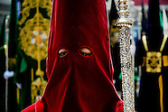 The female Holy Week participant wearing a red tunic and a hood with the conical hat (capirote) walks down the street during the Easter celebration in Malaga, Spain, 9 April 2007.