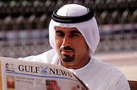United Arab Emirates. Dubai.  Businessman reading local newspaper in English..