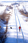 A hunter and his dog walk along a snow-covered rail line in search of a good place to shoot some wildlife.