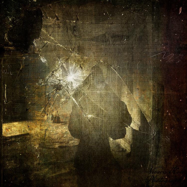Abstract self portrait taken in the reflection of a broken window.
