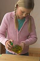 Mädchen macht Heilöl mit Gänseblümchen und Olivenöl, zerkleinerte Gänseblümchen werden in ein Glas gefüllt, mit Öl übergossen und anschließend geschüttelt, Bellis perennis, Daisy