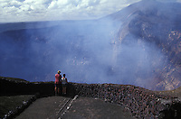 Tourists peering into the active crater of Volcan Masaya, Masaya Volcano National Park, Nicaragua