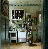 In the kitchen of an upstate New York farmhouse dating from the 1800s the rough plaster walls are painted oyster white with a grey frieze