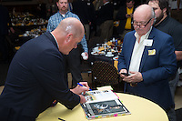 """Former Major League Baseball pitcher Jim Abbott autographs a book for one of the guests at the Wake Forest Baseball """"First Pitch"""" Dinner on February 9, 2017 in Winston-Salem, North Carolina.  (Brian Westerholt/Four Seam Images)"""