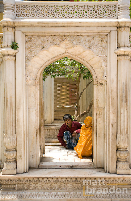A couple talks behind a marble arch in Nizamuddin.