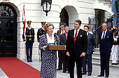 Washington, DC - (FILE) -- Prime Minister Margaret Thatcher of the United Kingdom, left, makes remarks after visiting United States President Ronald Reagan, right, at the White House in Washington, D.C. on Friday, July 17, 1987.  Also visible in the photo, from left, White House Chief of Staff Howard Baker (behind the President's left shoulder); United States Secretary of Defense Caspar Weinberger (behind the President's right shoulder); and United States Secretary of State George Schultz, far right. .Credit: Howard L. Sachs - CNP