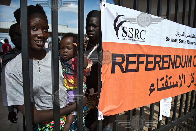 A mother waits with her baby at a registration centre where residents of the capital Juba can register for the South Sudan independence referendum scheduled for January 2011.