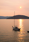 Idaho, North, Kootenai County, Coeur d'Alene. A sailboat rests offshore under smoky sunset skies on Lake Coeur d'Alene, In summer.