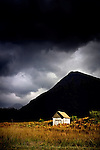 Shack and mountain beneath moody sky