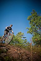 Descending a rock outcropping while mountain biking in Copper Harbor Michigan Michigan's Upper Peninsula.
