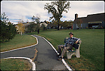 01172_02, Pennsylvania, USA, USA-10889. A man sits on a bench beside a pathway.