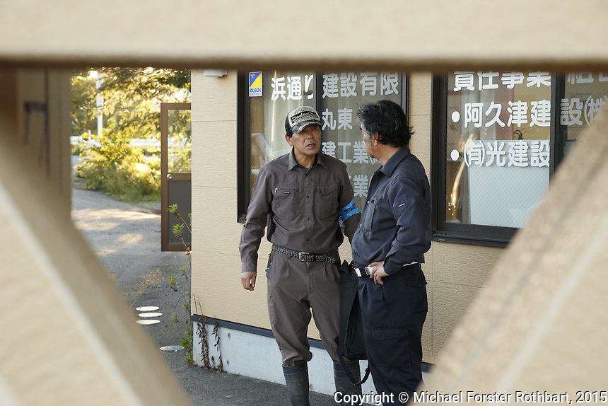 Decontamination laborers employed by the Maruto construction company meet outside the company&rsquo;s office in Tomioka, Japan, to report on their progress at the end of the day. In 2015, four and a half years after the Fukushima Daiichi nuclear power plant disaster, workers are decontaminating homes and commercial properties. Almost all developed properties in Tomioka are now getting cleaned or demolished. Full caption to come.<br /> <br /> &copy; Michael Forster Rothbart Photography<br /> www.mfrphoto.com &bull; 607-267-4893<br /> 34 Spruce St, Oneonta, NY 13820<br /> 86 Three Mile Pond Rd, Vassalboro, ME 04989<br /> info@mfrphoto.com<br /> Photo by: Michael Forster Rothbart<br /> Date:  10/2/2015<br /> File#:  Canon &mdash; Canon EOS 5D Mark III digital camera frame B19424