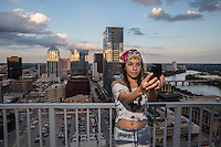 Local Austin Woman Taking Selfie with the Austin skyline, Lady Bird Lake from high-rise condo balcony during sunset in downtown Austin, Texas.
