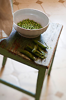 Detail of a bowl of freshly shelled peas on an old wooden kitchen chair