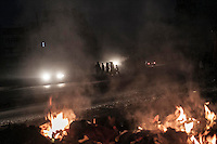 In this Saturday, Oct. 27, 2012 photo. Syrian residents walk crossing a street as a pile of rubbish burns at the roadside in Aleppo City, the largest city of Syria. (AP Photo/Narciso Contreras).