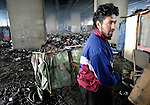 Arden Dasi, a refugee from Kosovo, pulls his recycling cart in a Roma settlement where he lived under a highway bridge in Belgrade, Serbia, when this photo was taken in February 2012. The families that lived here, most of whom survive from recycling cardboard and other materials, were forcibly evicted in April 2012. Many were moved into metal shipping containers on the edge of Belgrade..