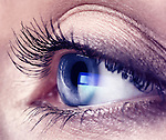 Closeup of a young woman eye with blue computer screen reflection in it