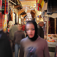 People walking and shopping in a souk in the medina of Fes, Fes-Boulemane, Northern Morocco. The medina of Fes was listed as a UNESCO World Heritage Site in 1981. Picture by Manuel Cohen