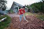Dailami smooths out fill material around his house in the Lam Pulo neighborhood of Banda Aceh, Indonesia, which was leveled in 2004 when a massive tsunami swept over the city. The Katahati Institute and Diakonie Katastrophenhilfe built 70 new houses in the neighborhood, including four for orphans, struggling and succeeding in titling them in the name of the children. The construction of a nearby mosque in 2014 has caused drainage problems, requiring residents to raise the level of the soil surrounding their homes. His wife Roslaini works in the background. The tsunami killed 221,000 people in Aceh province and left more than 500,000 displaced.